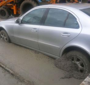 Mulher interrompe trânsito por várias horas. Estacionou um Mercedes em cima de cimento fresco!